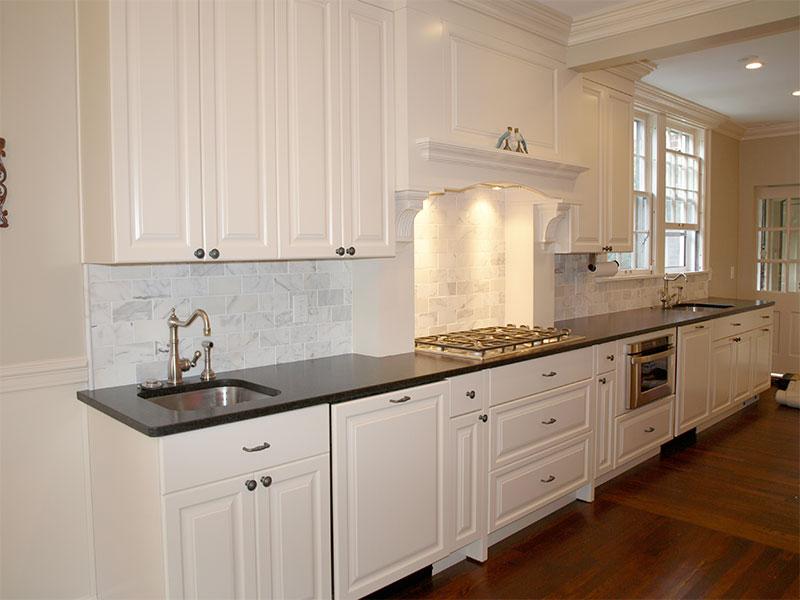 Dark granite counter tops with custom white marble backsplash to ...